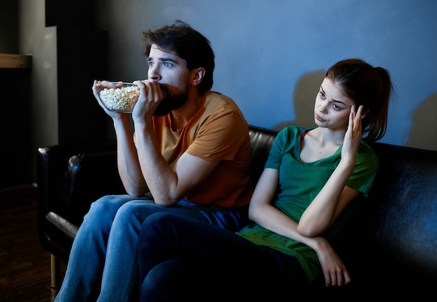 Young family sitting on the couch watching movies popcorn