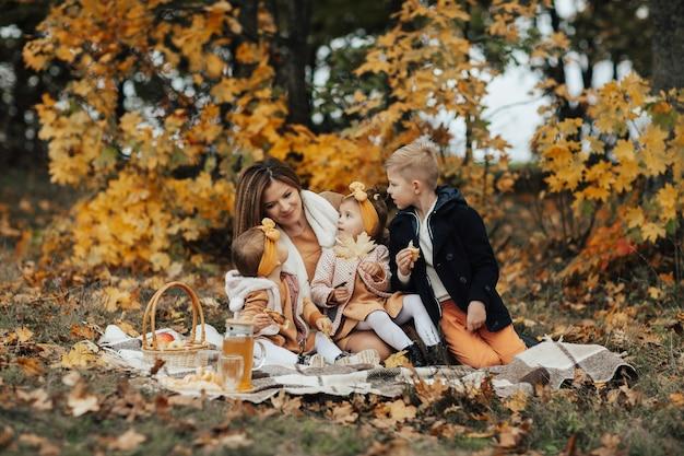 ピクニック毛布の上に座って、自然の中で美しい秋のピクニックを抱きしめて楽しんでいる若い家族。