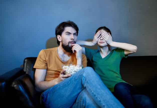 Молодая семья сидит на диване и смотрит фильмы с попкорном