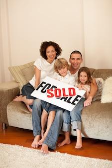 Молодая семья, сидя на диване с плакатом