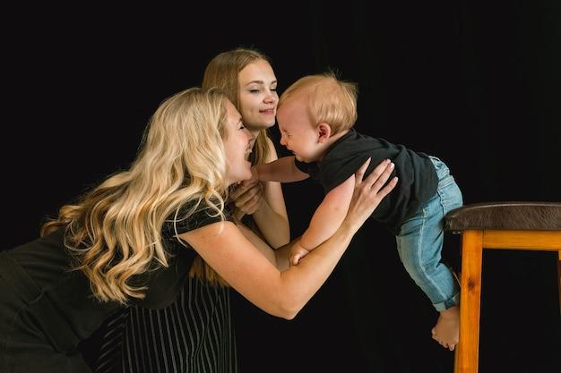 一緒に時間を過ごし、笑顔の若い家族。若い娘と幼い息子が遊んで笑っているお母さん。家族のライフスタイル。母の日、父の日、一体感、親子関係、子供の権利の概念。