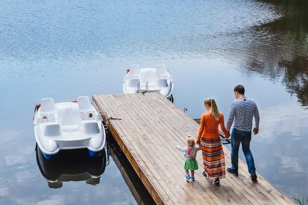 小さな娘と一緒に屋外の湖の近くで時間を過ごす若い家族