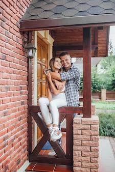 Молодая семья стоит на крыльце дома и обнимается.