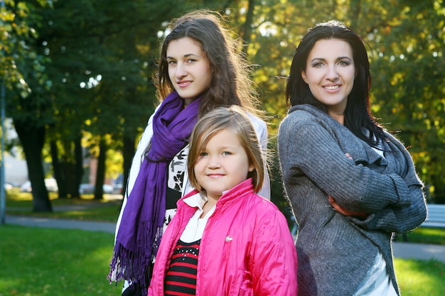 Young family taking healthy stroll through autumn park