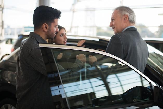 판매원과 이야기하고 쇼룸에서 새 차를 선택하는 젊은 가족