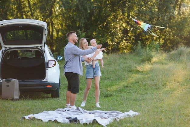 Молодая семья из трех человек в белых одеждах на пикник. красивые родители и дочь путешествуют на машине во время летних каникул. сцена в парке