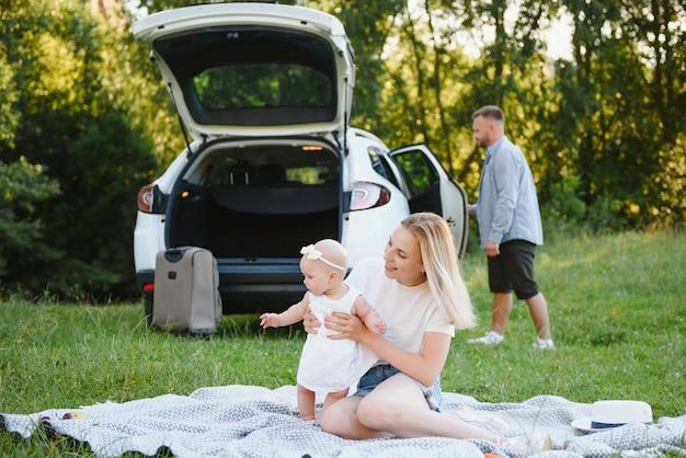 Молодая семья из трех человек в белых одеждах на пикник. красивые родители и дочь путешествуют на машине во время летних каникул.