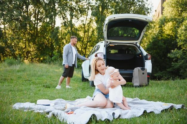 흰 옷을 입은 젊은 가족 3명이 피크닉을 합니다. 아름다운 부모와 딸은 여름 방학 동안 차로 여행합니다.