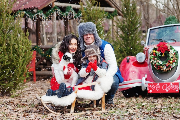 Young family of three posing with husky puppy against red christmas car in the forest.