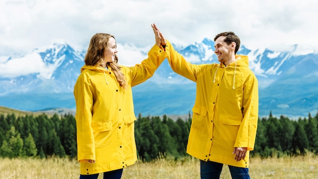 Young family together on vacation in the mountains. man and woman give high five outdoors, hiking in the alps, adventure, lifestyle, positive emotions. travel and trip concept