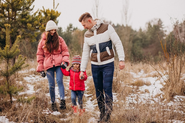 Young family together walking in forest at winter time