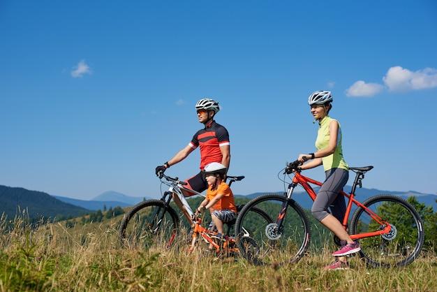 Молодые семейные туристы байкеры, мама, папа и ребенок отдыхают на велосипедах