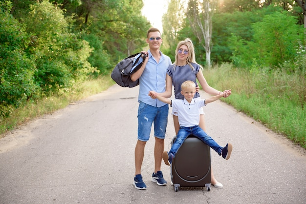 Young family traveller hitch hiking on empty road