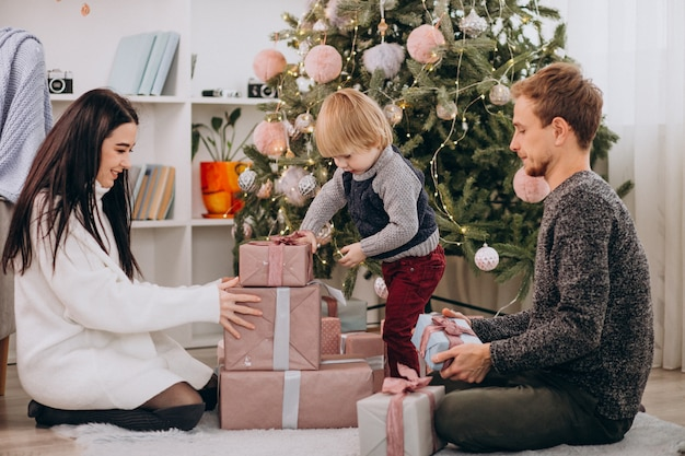 Young family unpacking gifts with little son by christmas tree