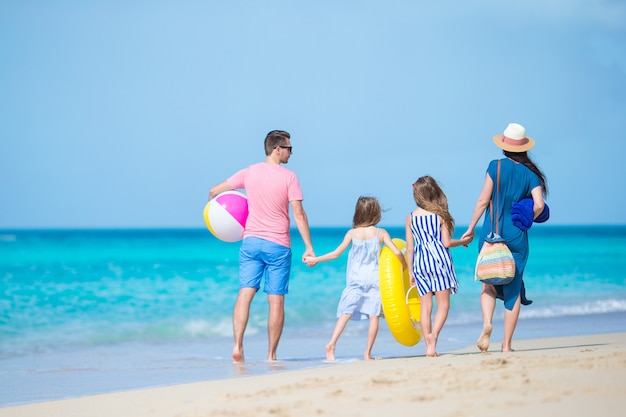 Young family on vacation have a lot of fun together. parents and kids going to swim