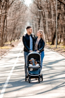 Young family walk in the park in the spring with a toddler in a stroller. happy parents