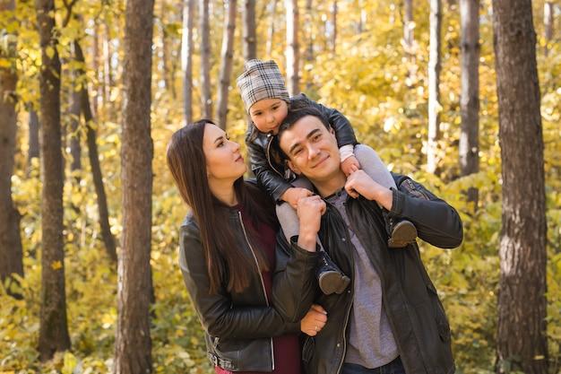 秋の公園を歩いている若い家族。