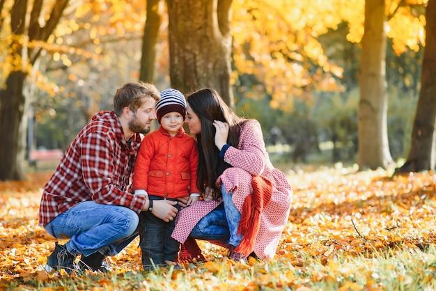 Молодая семья гуляет в парке. осень.