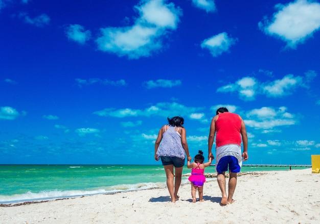 해변의 해 안에 모래에 걷는 젊은 가족. 바다 근처에서 아기의 손을 잡고 부모