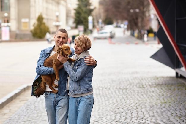도시 거리를 강아지와 함께 산책하는 젊은 가족