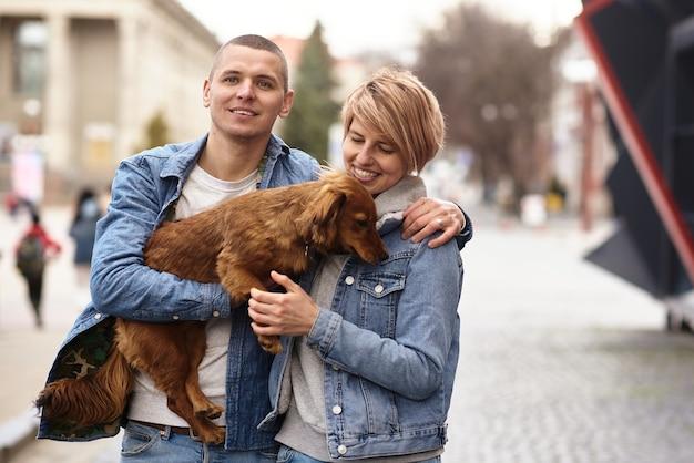 도시 거리를 개와 함께 걷는 젊은 가족