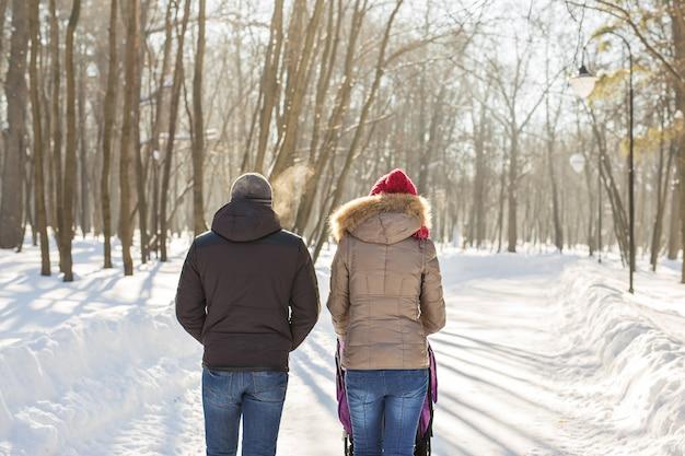 公園でベビーカーと一緒に歩いている若い家族。