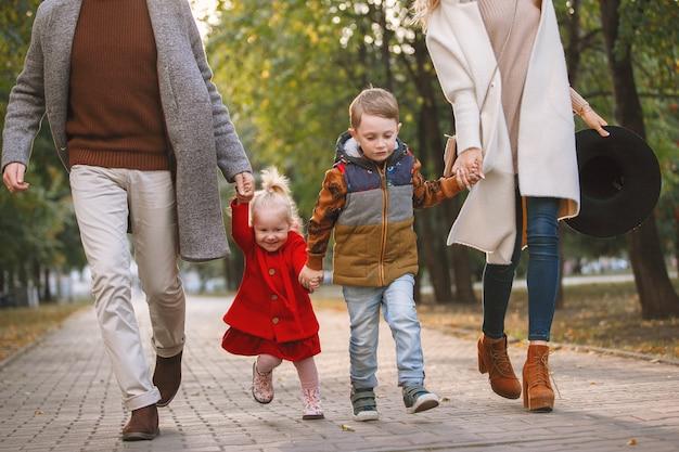 若い家族が公園の舗装路地を歩いています。彼は灰色のコートと黒い眼鏡をかけていて、彼女は白で、女の子は赤で金髪です。