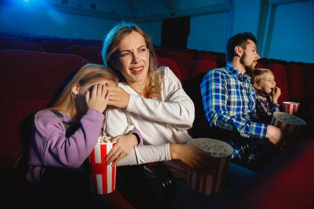 映画館で映画を見ている若い家族
