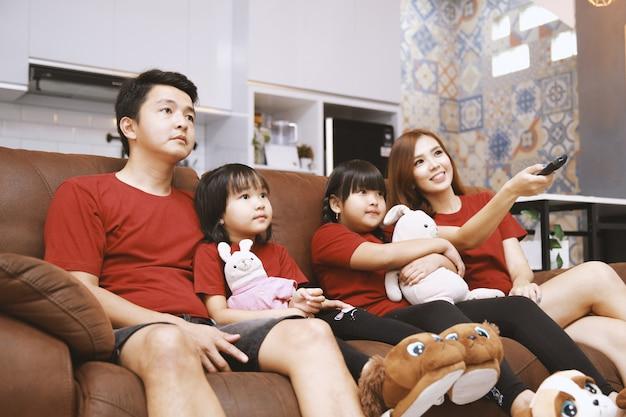 Молодая семья вместе смотрит телевизор дома и вместе веселится
