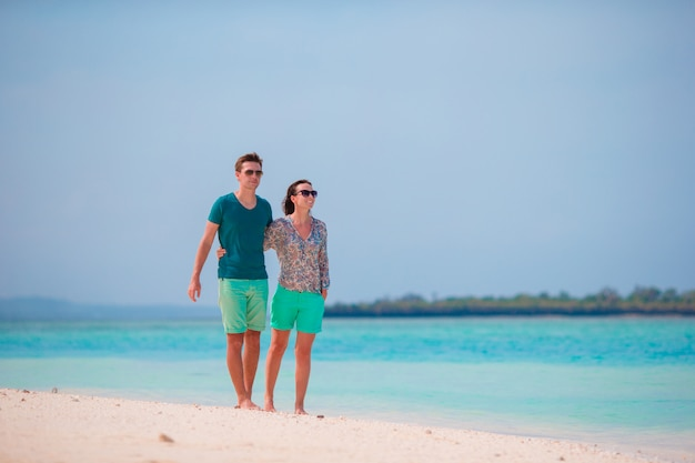 Young family on white beach during summer vacation. happy lovers enjoy their honeymoon at exotic island