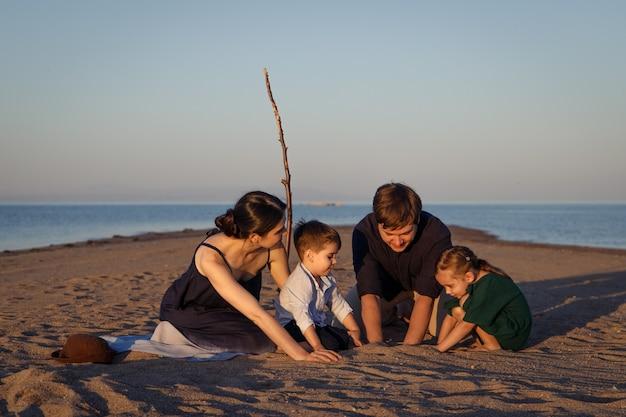 무인도의 해변에서 노는 2명의 자녀를 둔 젊은 가족.