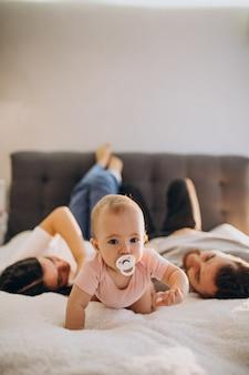 Giovane famiglia con bambina sdraiata insieme a letto