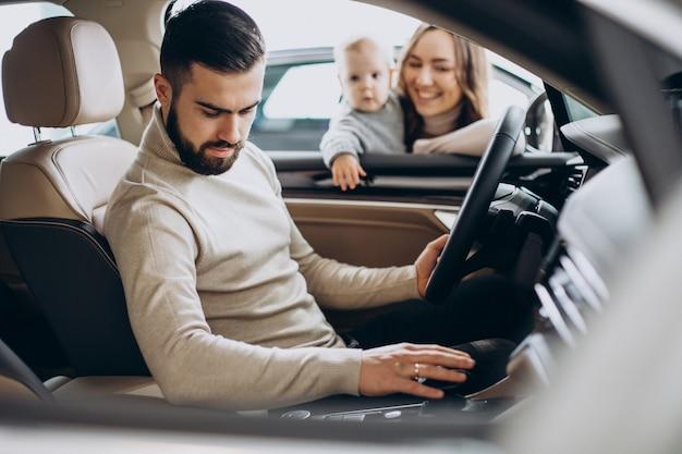 車を選ぶ女の赤ちゃんを持つ若い家族
