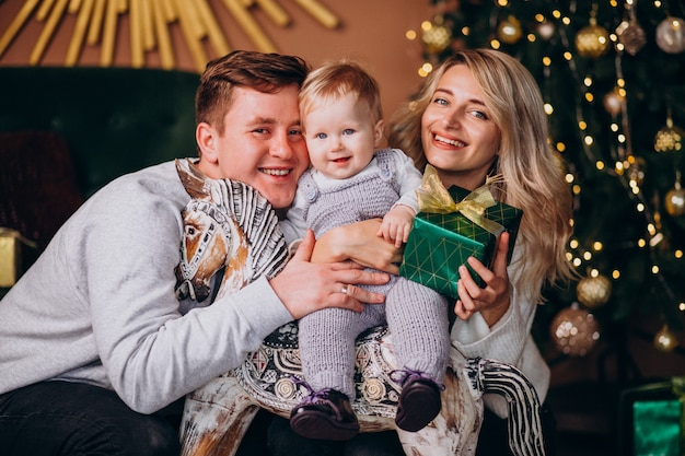 Young family with baby girl sitting by christmas tree