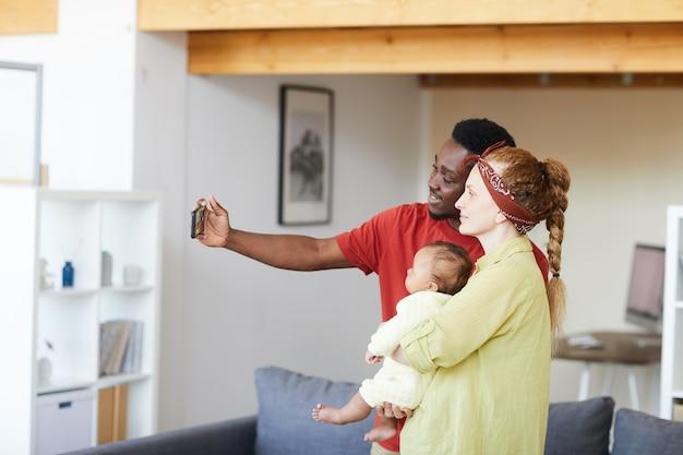 Молодая семья с ребенком делает селфи портрет на мобильном телефоне, стоя в комнате