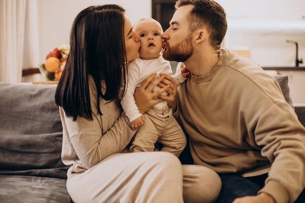 Молодая семья с малышом девочка дома, сидя на диване