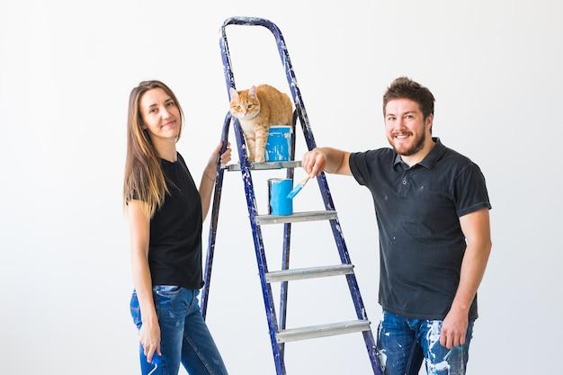 Молодая семья с кошкой занимается ремонтом и покраской
