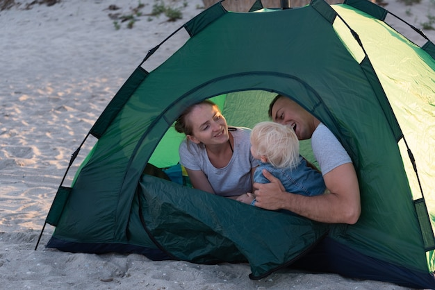 Young family with child in green tourist tent at the campsite. vacation with children.