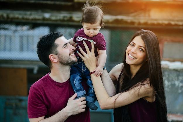 Молодая семья с ребенком позирует на заброшенном здании