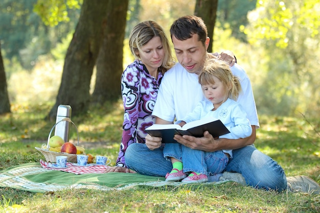 ピクニックで自然の中で聖書を読んでいる子供を持つ若い家族
