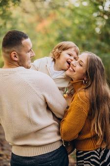 Giovane famiglia con bambini nella sosta di autunno