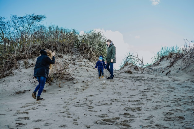 A young family with children spends the weekend on the shores of the cold baltic sea