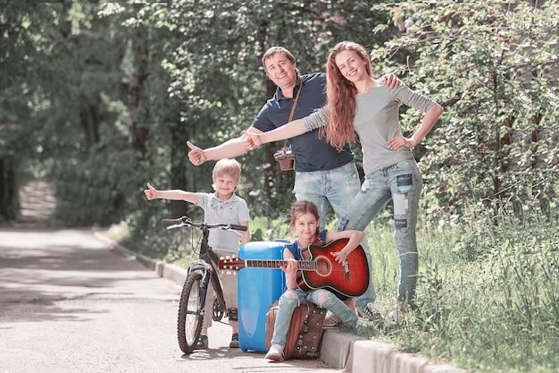 Молодая семья с детьми, путешествующая автостопом