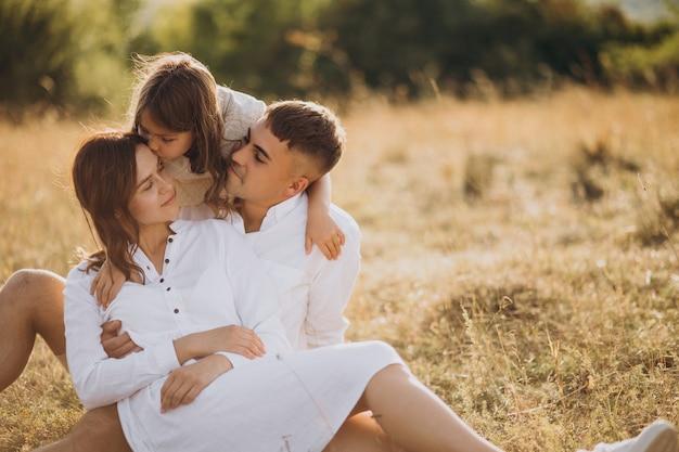牧草地で娘と若い家族