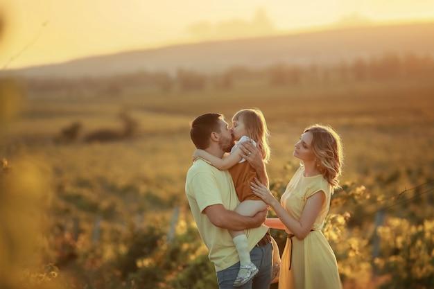 山で草を歩く娘と若い家族