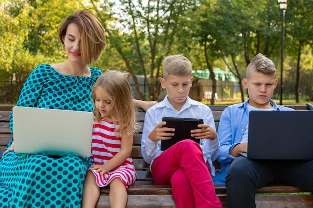 公園のベンチに座っているガジェットを持つ若い家族