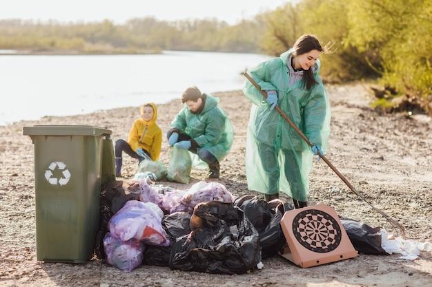 ゴミ袋を片付けている若い家族