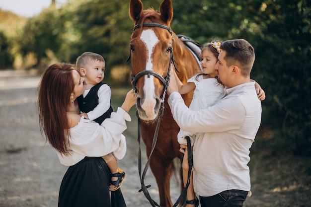 Young family with kids having fun with horse in forest