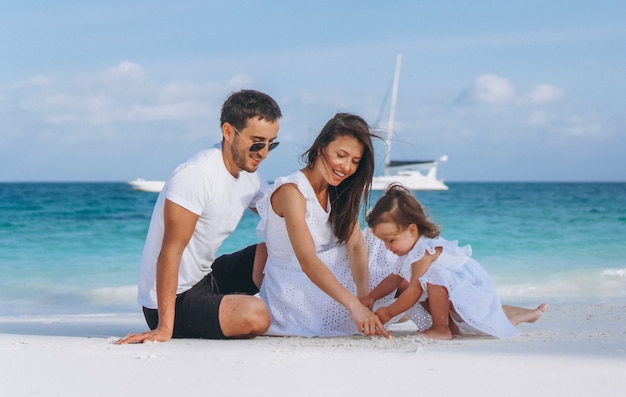Young family with little daugher on a vacation by the ocean