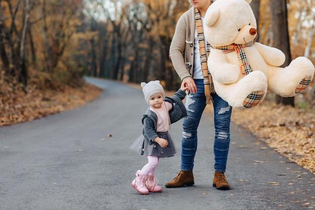 秋の公園道路で大きな娘と若い家族